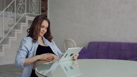 предродовой : Happy pregnant woman sitting at a glass kitchen table drinking coffee and using a tablet computer. Engaged in business on the Internet Стоковые видеозаписи