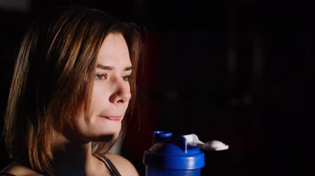 toalha : Gorgeous young woman with a towel on her neck drinking water from a bottle at the gym. Stock Footage