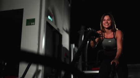 squatting : Female athlete working out with heavy ropes at the gym.