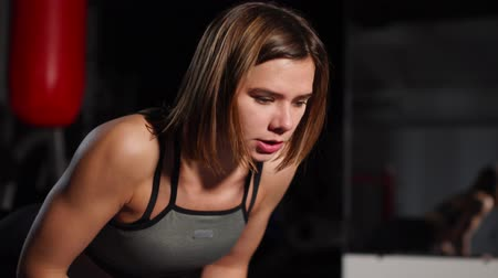 planking : A brunette athletic builds push-ups on a mache in the gym putting a stopwatch on the mobile phone. Boxing training, Combat sports. Stock Footage