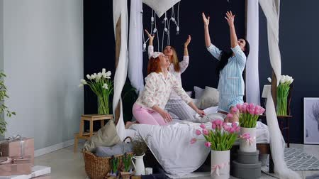 yatak kıyafeti : Three young sexy women pillow fighting at a slumber party in honor of the wedding. Beautiful woman laughing and smiling playfully. A pajama party. Dancing on the bed. Stok Video