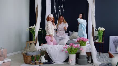 yatak kıyafeti : Three young sexy women pillow fighting at a slumber party in honor of the wedding. Beautiful woman laughing and smiling playfully. A pajama party. Dancing on the bed with her friends.