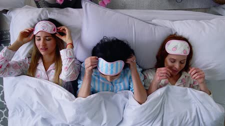 bachelorette party : Top view, three beautiful girls go to sleep on the bed and put eye bandages to sleep.