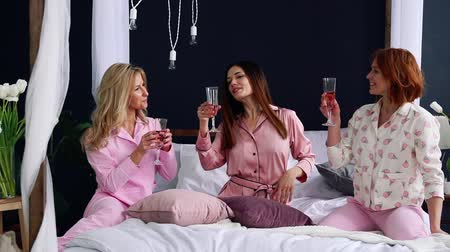yatak kıyafeti : Three beautiful girls sitting on the bed in pajamas knock glasses of champagne laugh and smile.