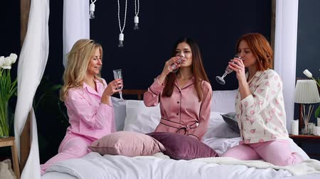 yatak kıyafeti : Three beautiful girls sitting on the bed in pajamas knock glasses of champagne laugh and smile. Pajama party
