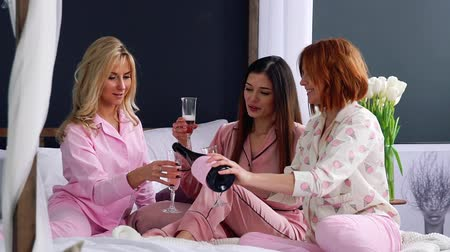 yatak kıyafeti : Three beautiful girls sitting on the bed in pajamas banging glasses of champagne talking about the upcoming wedding and talking toast to each other laughing and smiling at each other. Pour champagne from a bottle to friends.
