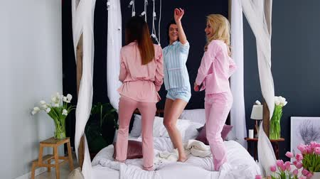 filho : Pajama party before the wedding three bridesmaids dance on the bed laughing and looking at the camera. Bachelorette party pre-wedding party. Sexy Asses moving to the rhythm of music