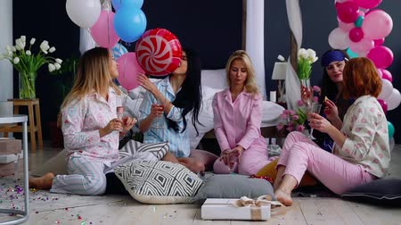 impending : The bridesmaids sitting in a circle bumping glasses with champagne wishes and say happy for the impending marriage. Congratulations on the happy event. Womens pre-wedding party. Laughter and joy. Bridesmaid. Pajama party Stock Footage