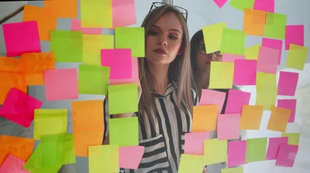 клейкий : Creative business team brainstorming ideas working together sharing data late at night after hours in modern glass office. Two very beautiful girls in office clothes blonde and brunette with glasses look at the colored stickers and offer ideas Стоковые видеозаписи