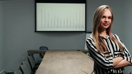 šklebící : Portrait of a sexy blonde business woman in office clothes standing in the office against a large table and graphs on the screen looking at the camera