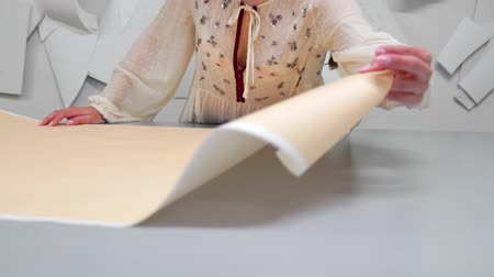 рукоделие : Young female designer with tape-line on her neck standing in dressmaking studio and drawing lines with chalk and rule. Female couturier in atelier cutting out a pattern for future clothes. Стоковые видеозаписи