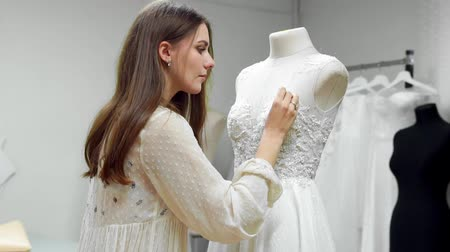 white cloths : Portrait of a girl creating a wedding dress by exclusive order sewing fabrics and rhinestones on a dress dressed in a mannequin. production of wedding dresses. Little business Stock Footage