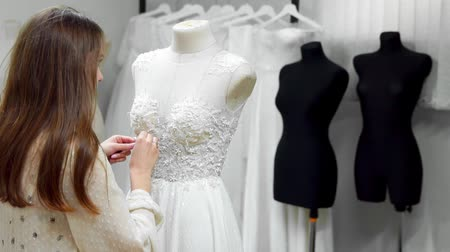 шить : Portrait of a girl creating a wedding dress by exclusive order sewing fabrics and rhinestones on a dress dressed in a mannequin. production of wedding dresses. Little business Стоковые видеозаписи