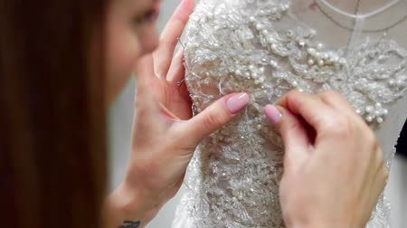 koronka : Close-up fashion designer for brides in his Studio pins needles lace wedding dress. Seamstress creates an exclusive wedding dress. Secure with pins and needles outline. Small private business. Sew rhinestones and crystals to the dress thread and needle. J