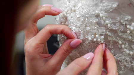sobre o branco : Close-up fashion designer for brides in his Studio pins needles lace wedding dress. Seamstress creates an exclusive wedding dress. Secure with pins and needles outline. Small private business. Sew rhinestones and crystals to the dress thread and needle. J