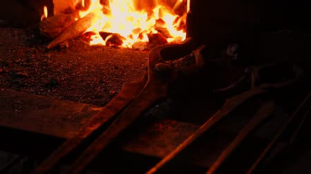 zanaat : Closeup of a blacksmith fanning the flames of the furnace, using the tools prevents embers, sparks flying to the side in slow motion. Close-up of blacksmiths hand.