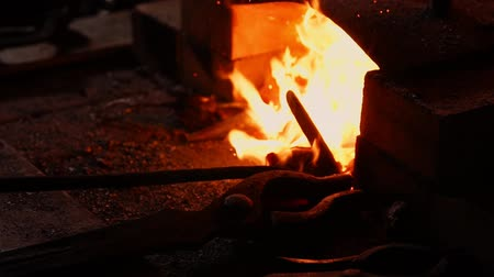 charcoal stove : Closeup of a blacksmith fanning the flames of the furnace, using the tools prevents embers, sparks flying to the side in slow motion. Close-up of blacksmiths hand.