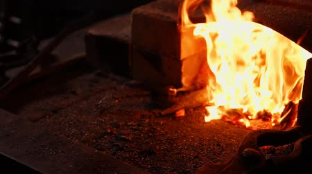 metal işi : Closeup of a blacksmith fanning the flames of the furnace, using the tools prevents embers, sparks flying to the side in slow motion. Close-up of blacksmiths hand.