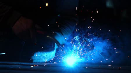 welding torch : The welder works in a mask in slow motion. Sparks fly in different directions. Blue color glow welding. Work with steel materials