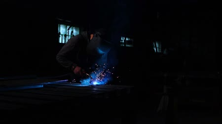 acetylene : The welder works in a mask in slow motion. Sparks fly in different directions. Blue color glow welding. Work with steel materials