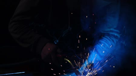 сварщик : The welder works in a mask in slow motion. Sparks fly in different directions. Blue color glow welding. Work with steel materials