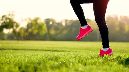 daily : At sunset in a field of sporty girl on the grass in a white top and pink sneakers makes the warm-up run before lifting hips. Sport. close up. Grass sneakers Stock Footage