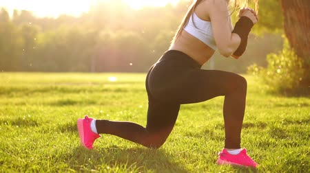 squatting : Young muscular fitness woman doing squats exercise in the nature. Stock Footage