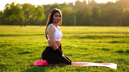 pózy : Young and beautiful woman is sitting on the mat during break in her fitness workout. Rest after exercise in the sunlight correcting the hair in slow motion. Hair in the backlight.
