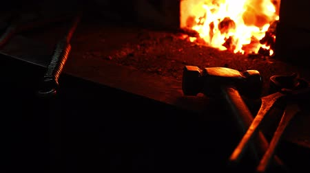 demirci : Closeup of a blacksmith fanning the flames of the furnace, using the tools prevents embers, sparks flying to the side in slow motion. Close-up of blacksmiths hand.