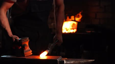 demirci : Closeup of a blacksmiths hammer on the background of burning flames of the furnace. Stok Video