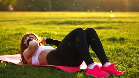 břišní : Woman doing abdominal crunches exercise on the fitness mat in summer park In slow motion at sunset. Dostupné videozáznamy