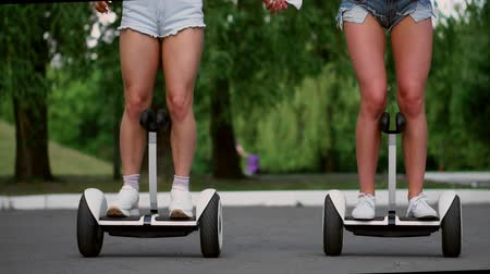 self balancing : Two sexy young girls riding on Segway in short shorts holding hands and laughing on a Sunny day in the Park