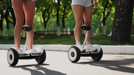 self balancing : Beautiful shapely legs young girls in short chertah closeup on white gyrometer the electric hoverboard ride through the Park