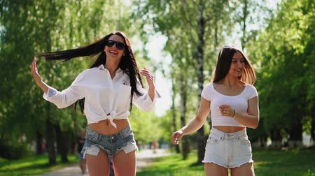 self balancing : Beautiful slender brunette girls in sunglasses white tops and short hair have fun and laugh dancing on white hoverboard in the Park
