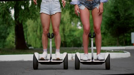 self balancing : Two sexy young girls riding on hoverboard in short shorts holding hands and laughing on a Sunny day in the Park Stock Footage