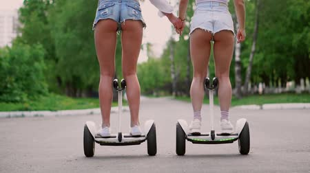 self balancing : Sexy girls in short denim shorts ride on white hoverboard close - up slow motion Stock Footage
