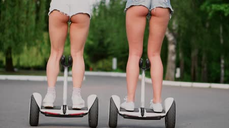 self balancing : Sexy girls in short denim shorts ride on white Segways close - up slow motion