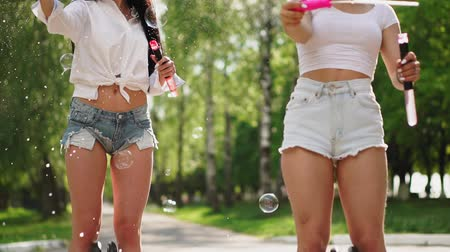 self balancing : Two beautiful young girls in sexy clothes are laughing and dancing while riding a in the Park on the weekend playing with soap bubbles in slow motion