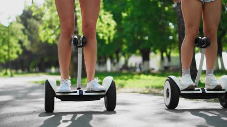 self driving : Two girls in short shorts ride the camera and smile at the self-balancing scooter in the Park