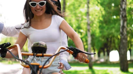 self balancing : Two young and sexy brunette friends with loose hair in short denim shorts riding an electric motorcycle in the Park on a Sunny day enjoying hugging each other. Best friends spend time together Stock Footage