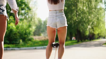 self balancing : Two girls in short shorts ride from the rear view camera on a self-balancing scooter in the Park