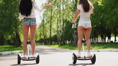 self driving : Two girlfriends riding on white hoverboard launch soap bubbles Stock Footage