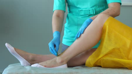 woman waxing : The girl talks on the phone and smiles during hair removal on the legs in the beauty salon. Hair removal on the legs with sugar. clouse-up