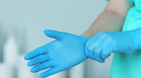 woman waxing : Close-up of the doctor wearing rubber gloves