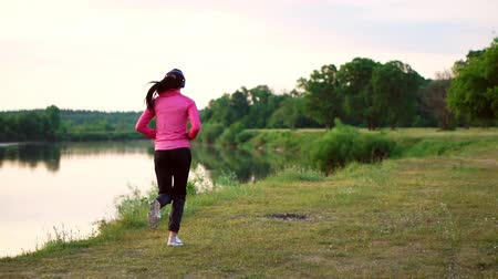 бегун трусцой : Brunette with long hair in headphones runs along the river in the Park in the morning at sunrise in the summer in a pink jacket and black pants