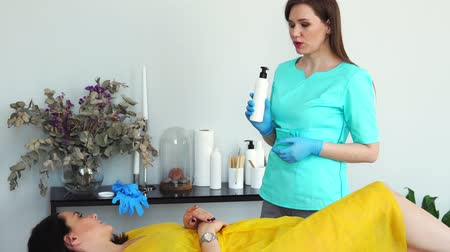 woman waxing : The girl is a master of hair removal with the help of shugaring advises the client to the girl about the possibilities of the procedure