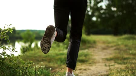 persons : Close-up of feet running in sneakers along the river on the grass