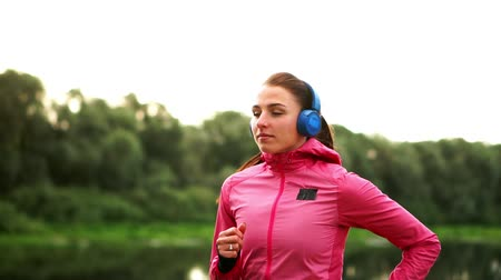 бегун трусцой : A girl in a pink jacket and black pants runs near the river in headphones preparing for the marathon Стоковые видеозаписи