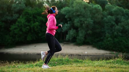спортивная одежда : A girl in a pink jacket and black pants runs near the river in headphones preparing for the marathon Стоковые видеозаписи