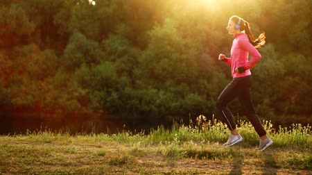 спортивная одежда : Brunette with long hair in headphones runs along the river in the Park in the morning at sunrise in the summer in a pink jacket and black pants